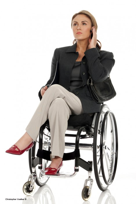 Young working woman who uses a wheelchair, holds folder and is on the phone.